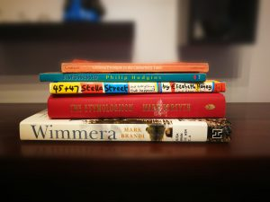 Five books stacked on top of each other with a blurred background