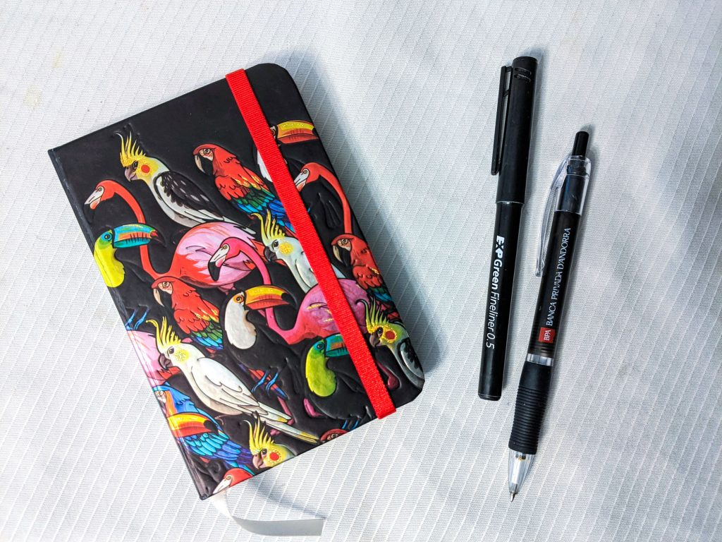 Notebook with brightly coloured birds on it, two black pens next to it, all on a white cloth