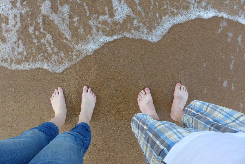 Two pairs of feet standing on sand, small wave coming up to meet them