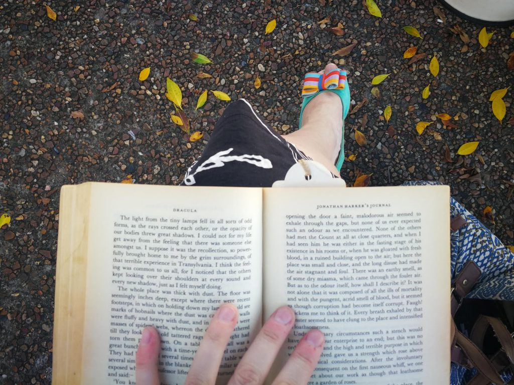 Looking down to a book open on my lap, cute shoes below