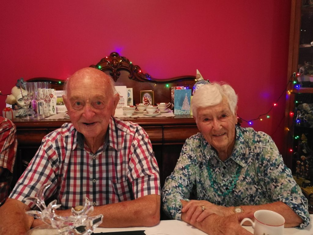 Elderly man and woman sitting at a table and smiling at the camera