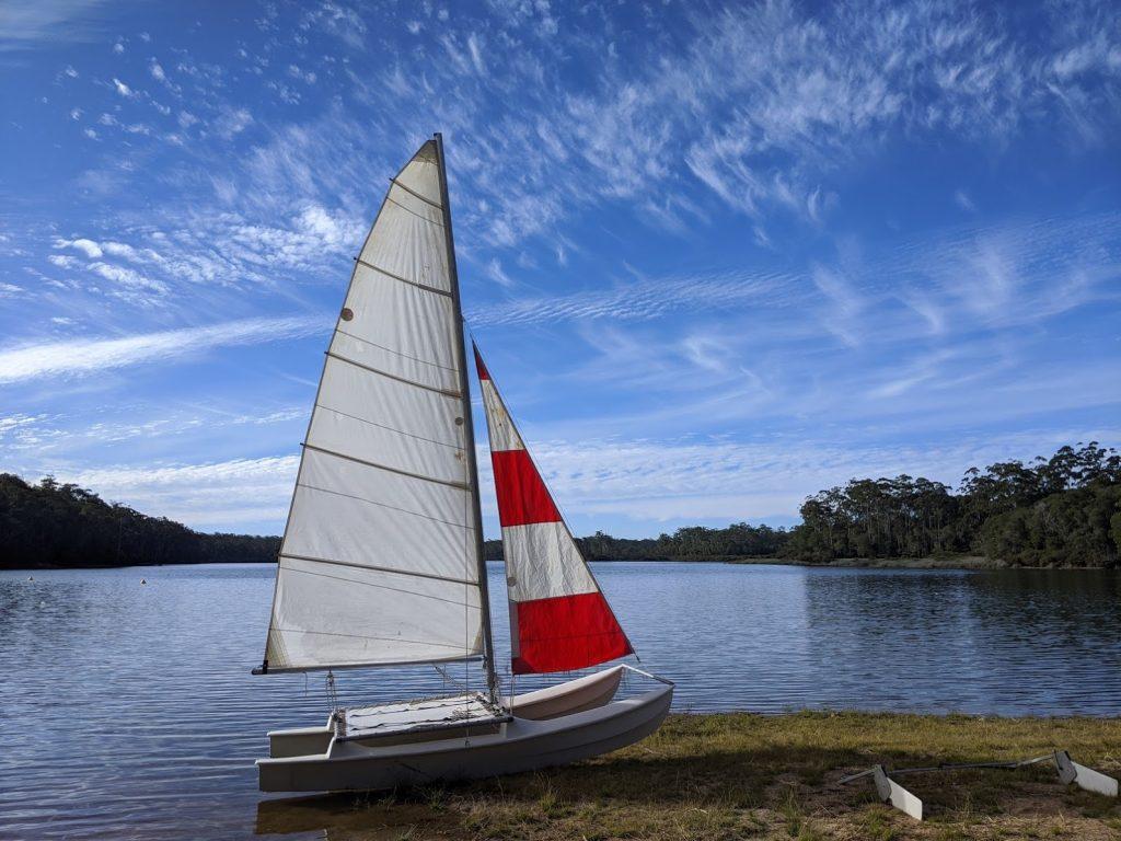 Small catamaran, sails up, on the banks of a lake
