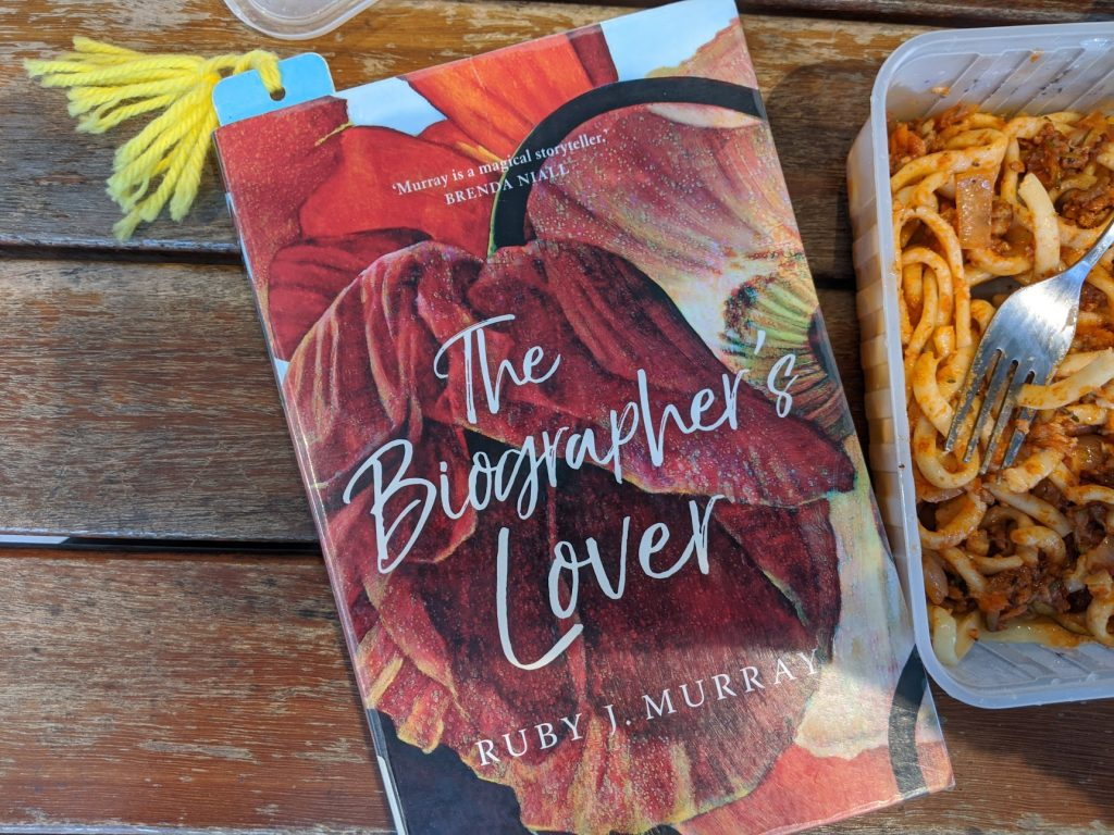 "book ""the biographer's lover"" on a wooden table next to a takeaway container of pasta with a fork in it"