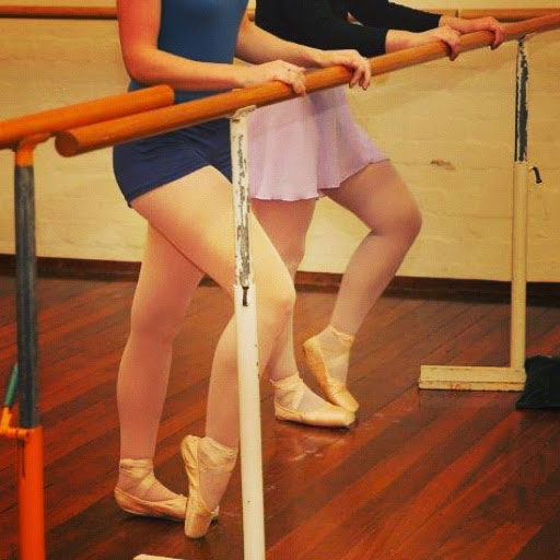 Cropped photo showing the lower body of two women in leotards, at the barre, wearing pointe shoes.
