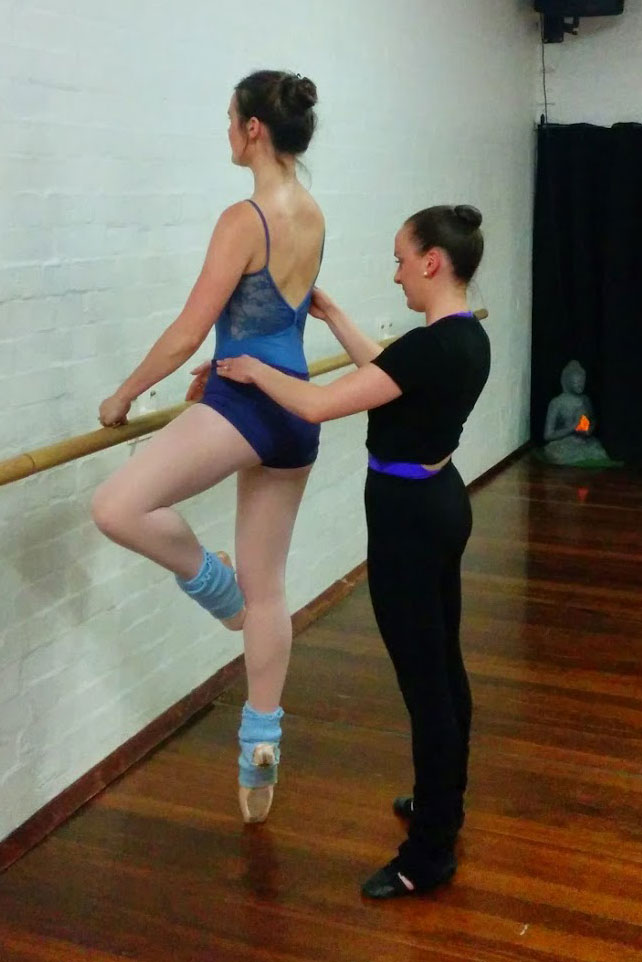 Bethany en pointe, en retire at the barre, back to the camera. The teacher is behind her, making adjustments to her position.