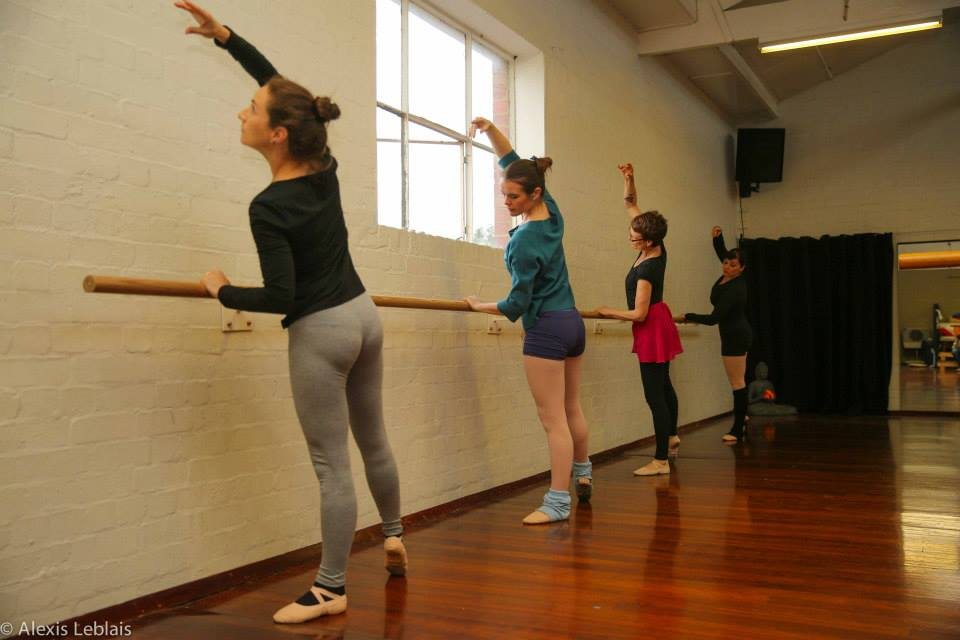 angled photo of four women at a ballet barre