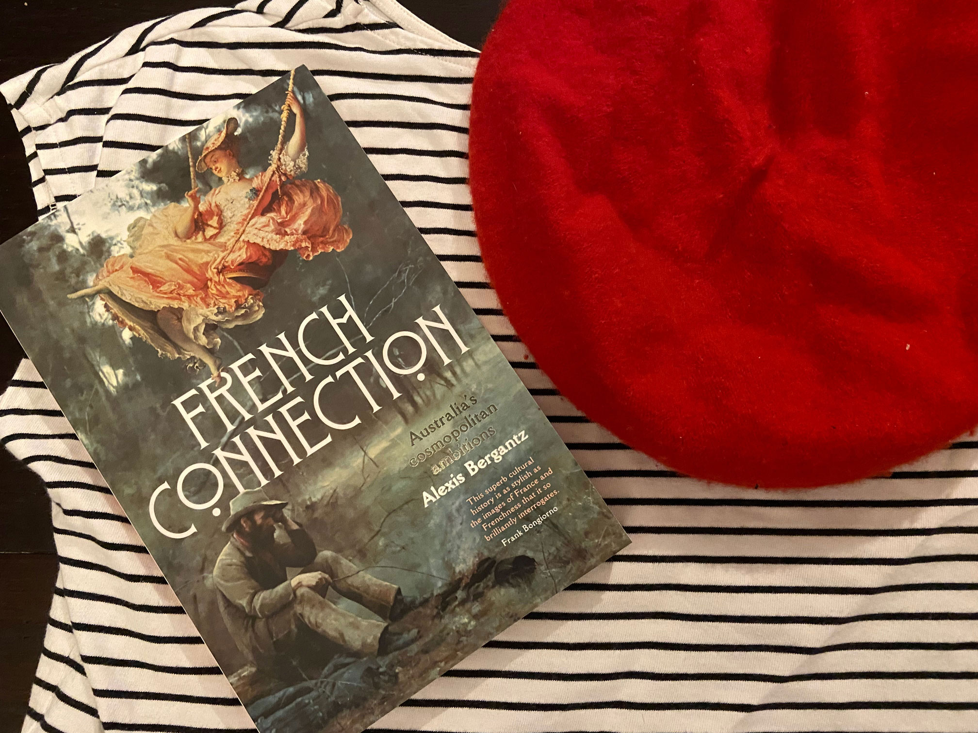 looking down at the book on top of a striped shirt and next to a red beret
